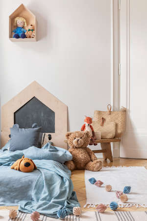 Real photo of a cozy child bedroom interior with a bed, toys and lamps chain on a floor