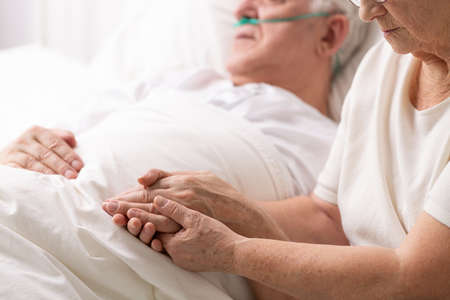 Senior grandmother holding hand of her cancer sick husband lying in white hospice bed, photo with copy space