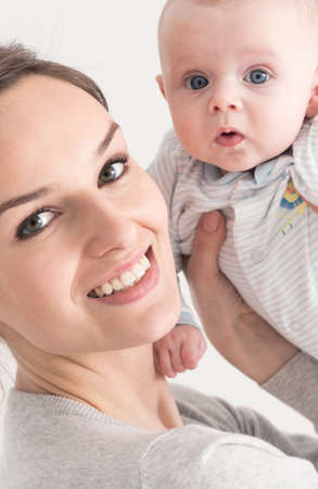 Smiling young mother holding up surprised infant Archivio Fotografico - 116186876