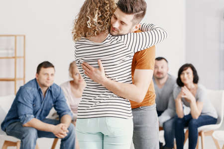 Man hugging woman after quarrel during therapy for couples with problems Banque d'images - 116186878