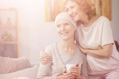Bright photo of two positive senior woman sitting together at home enjoining their time after cancer treatment Banque d'images - 116186879