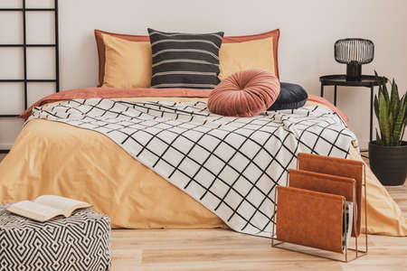 Open book on pouf and magazine organizer in the foot of a king size bed with yellow bedding and black and white blanket Foto de archivo - 116186972