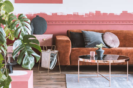 Trendy living room with ombre wall and brown velvet corner sofa with pillows Stockfoto