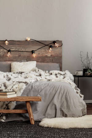 White fury blanket on grey bedding of king size bed with wooden headboard and lights