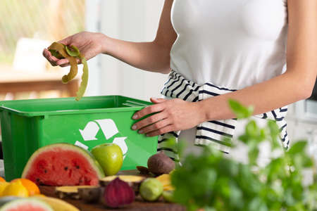 Close-up of a woman putting kiwi peeling into a recycling basket in her kitchen