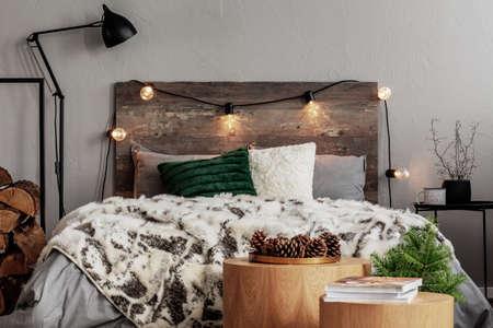 Design della camera da letto di Natale con luci, abete rosso e coni