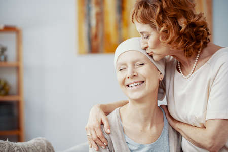 Senior redhead woman kissing forehead of her happy best friend suffering from cervical cancer