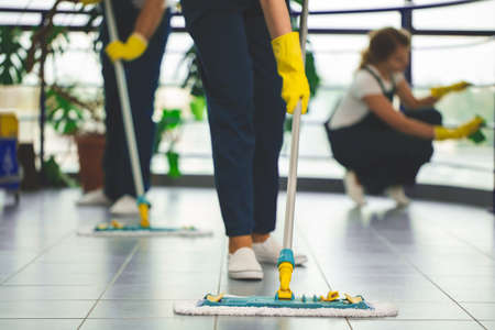 Close-up on person with yellow gloves holding mop while cleaning the floor