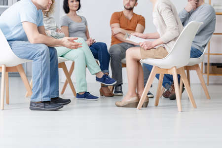 Close-up on psychotherapist talking with group of people with problems during therapy Banque d'images - 116187092