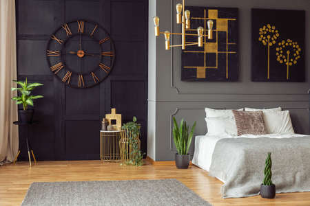 Dark bedroom interior in real photo with fresh plants, carpet on floor, double bed and gold lamp Banque d'images