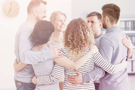 People hugging each other and supporting during group therapy for anonymous alcoholics Banque d'images - 116187096