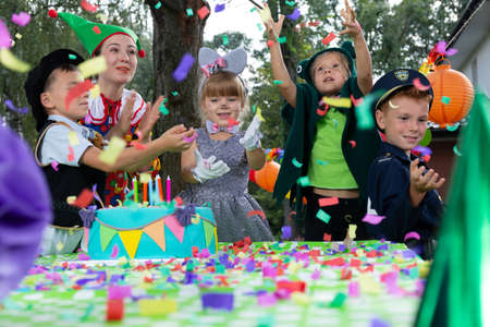Kids enjoying the confetti rain during birthday dressing up party in the garden Banque d'images - 116187097