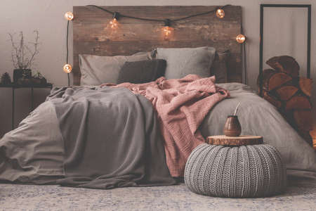 Pastel pink and grey blanket on grey bedding of king size bed in christmas decorated bedroom