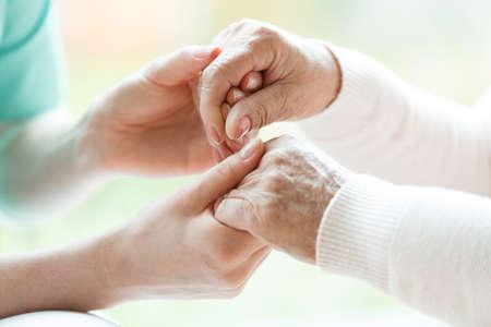 Close-up van de handen van een jonge verpleegster die de handen van een oudere dame vasthoudt Stockfoto