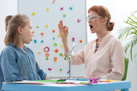 Speech therapist and girl learning vowels Stockfoto