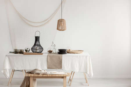 Rattan lamp above dining table with wicker plateau and black glass plates and elegant metal lantern, copy space on empty white wall