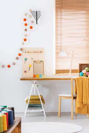 Boules de coton à l'intérieur du pigiste blanc avec couverture jaune sur chaise au bureau en bois. Vrai photo