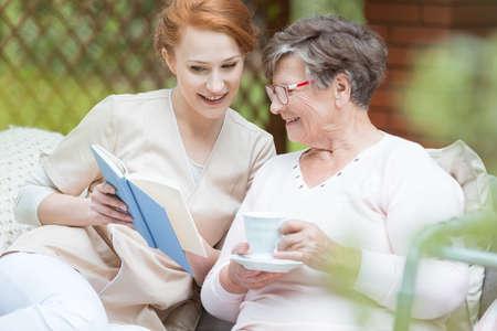 Beautiful redhead nurse shows photo album to senior lady in the garden