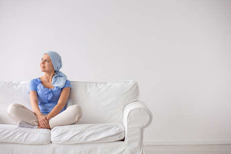 Smiling teenage girl suffering from leukemia, wearing blue headscarf and siting on the couch at home after radiotherapy, copy space on empty white wall Stock Photo