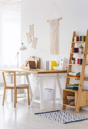 Wooden organizer next to desk with sewing machine in workspace interior with chair. Real photo