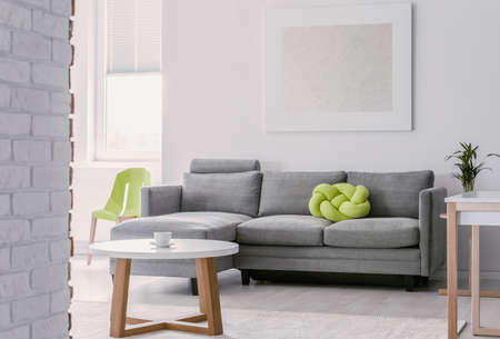 Lime green knot pillow on grey corner couch in bright living room with round white wooden coffee table, mockup painting on the empty white wall