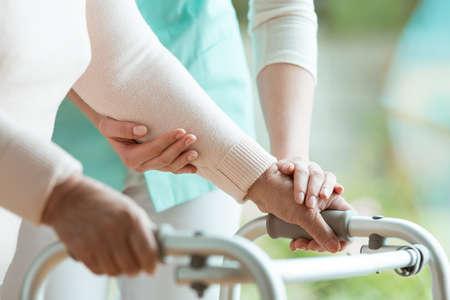 Gros plan des mains d'une dame âgée tenant un déambulateur et une infirmière de soutien l'aidant