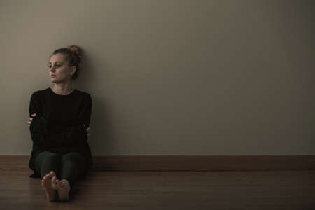 Picture of a sad teenage girl suffering from loneliness, sitting alone on the floor, copy space on empty wall