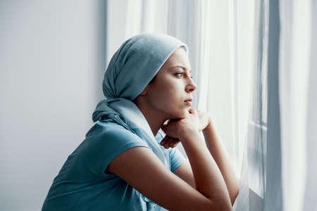 Nachdenkliches junges Mädchen, das an Knochenkrebs leidet, blaues Kopftuch trägt und nach der Operation im Krankenhaus durch das Fenster schaut