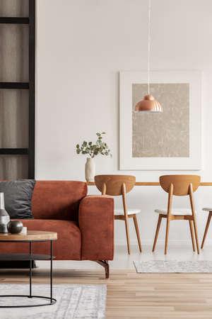 Wnętrze salonu i jadalni na otwartym planie z długim stołem z krzesłem i brązową aksamitną sofą