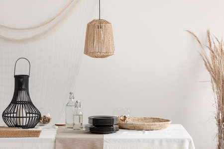 Rattan lamp above dining table with wicker plateau and black glass plates and stylish metal lantern, copy space on empty white wall 写真素材