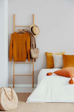 Close up on a bed and wooden decorating ladder with clothes