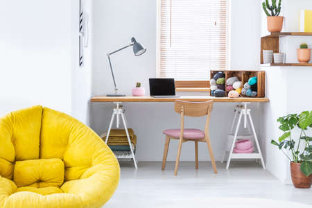 Yellow pouf in white home office interior with wooden chair at desk with lamp and laptop. Real photo Stock Photo