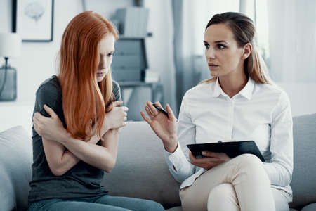 Red head teenage girl with post traumatic stress during meeting with her therapist