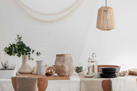 Green plant in beige vase, white jug and wicker lantern on dining table in bright interior Stock Photo