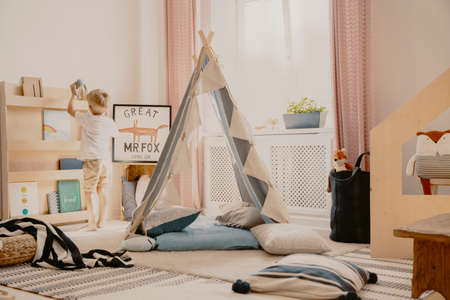 Cozy kids room with pastel colored curtains and scandinavian tent with pillows, real photo
