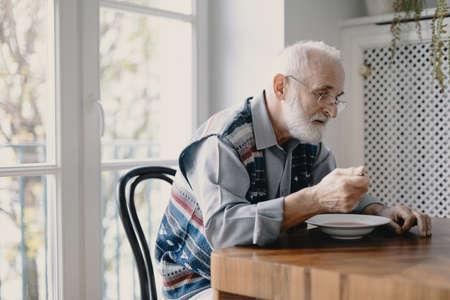 Älterer Großvater mit grauen Haaren und Bart, der alleine in der Küche sitzt und frühstückt