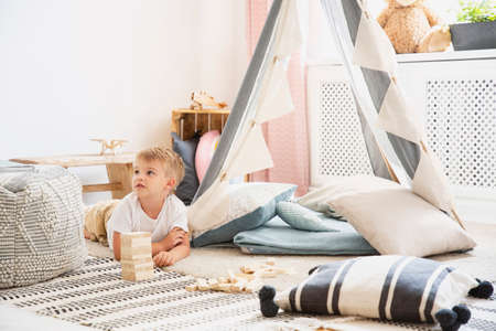 Cute little boy lying on the floor of scandinavian playroom with grey tent with cozy pillows and patterned carpet, real photo with copy space Stock Photo