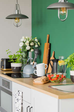 Bread and vegetable salad on wooden counter of trendy kitchen