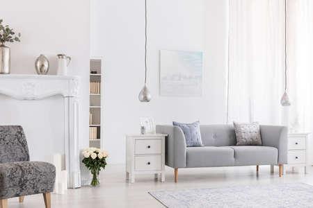 Kussens op grijze bank in wit woonkamerinterieur met bloemen in de buurt van fauteuil met patroon. echte foto