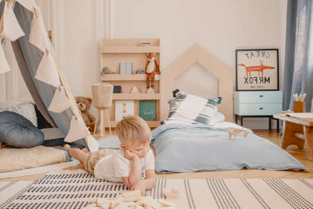 Cute little boy laying on the floor of his stylish scandinavian bedroom, real photo