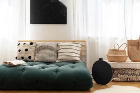 Straw handbags next to stylish black vase and fancy sofa with pillows made of futon, black poster on the wall between windows Standard-Bild