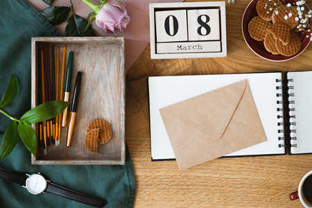 High angle photo of wooden table with envelope placed on notebook, box with brushes and pens and cookies in bowl
