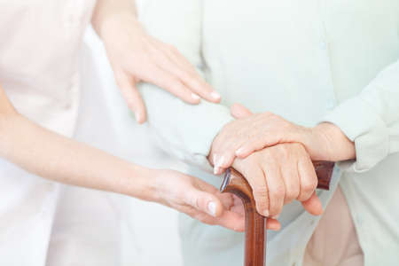 Closeup of senior ladys hands on wooden walking stick, helpful nurse supporting her