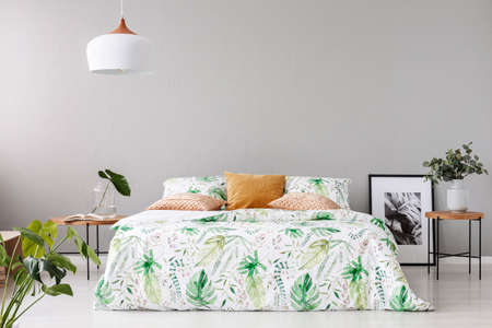 Double bed with floral duvet and peach colored pillow between two wooden nightstands with flowers in vases on it