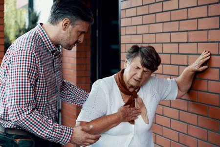 Hijo tratando de ayudar a su madre que tiene dificultad para respirar Foto de archivo