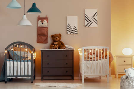 Warm baby bedroom interior with white and grey cribs, commode and small nightstand table with lamp Stock Photo