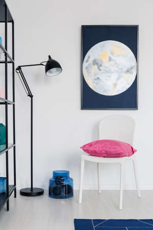 Vertical view of white chair with pink pillow in white interior with moon graphic on the wall and metal lamp, real photo Stock Photo