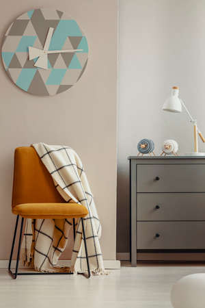 Stylish yellow chair in elegant interior with grey wooden chest of drawers