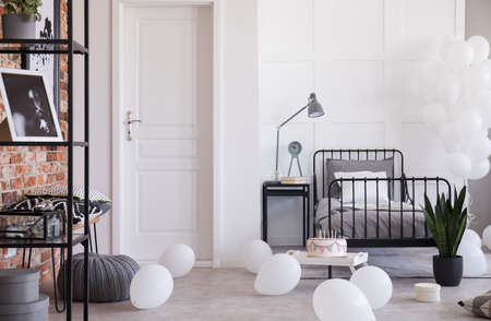 Grey lamp and clock on nightstand next to single metal bed in industrial bedroom with balloons Stock Photo