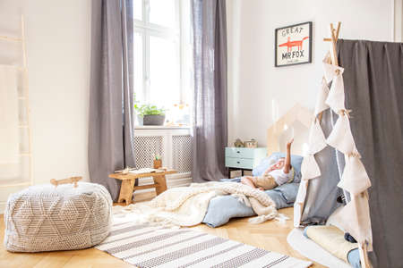 Comfortable bed in scandinavian kids bedroom with grey tent and big pouf, real photo with mockup on the wall